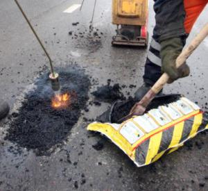 Дорожники латают Крестовоздвиженский мост после того, как несколько автомобилистов повредили в ямах колеса